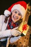 Donna felice vicino a Palazzo Vecchio che mostra la scatola del regalo di Natale Immagini Stock Libere da Diritti