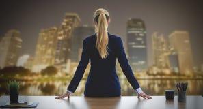 Donna femminile di affari che guarda fuori le finestre per il busin di notte immagini stock