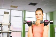 Donna femminile di forma fisica che fa il suo allenamento con le teste di legno in palestra Fotografie Stock