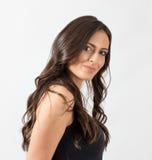 Donna femminile splendida con capelli ondulati lunghi che esaminano macchina fotografica Fotografia Stock