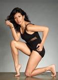 Donna figurata dei capelli neri che osserva nella macchina fotografica immagine stock
