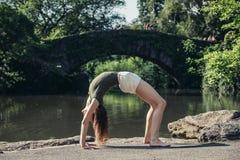 Donna flessibile che fa posa di yoga nel parco della città a New York immagini stock libere da diritti