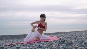 Donna flessibile di yoga sulla spiaggia archivi video