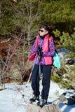 Donna fornita che fa un'escursione in un'alta montagna di inverno Immagini Stock