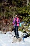 Donna fornita che fa un'escursione in un'alta montagna di inverno Fotografie Stock