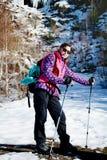 Donna fornita che fa un'escursione in un'alta montagna di inverno Fotografia Stock
