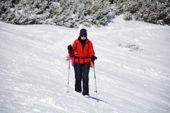 Donna fornita della viandante che fa un'escursione in un'alta montagna di inverno Fotografie Stock