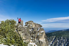 Donna fornita della viandante che fa un'escursione in un'alta montagna sulle rocce Fotografie Stock Libere da Diritti