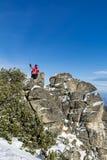 Donna fornita della viandante che fa un'escursione in un'alta montagna sulle rocce Fotografia Stock