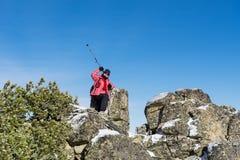 Donna fornita della viandante che fa un'escursione in un'alta montagna sulle rocce Immagini Stock