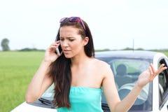 Donna frustrata che per mezzo del telefono cellulare contro l'automobile ripartita Fotografie Stock
