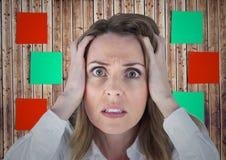 Donna frustrata con le mani sul suo fronte contro la nota appiccicosa su fondo di legno immagini stock