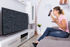 Donna frustrata con un impulso errato dello schermo della TV fotografia stock