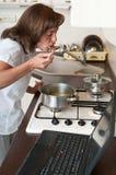 Donna a funzioni multiple - cucinare pasto e funzionare immagini stock