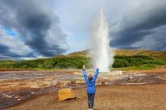 Donna - geyser contentissimo Strokkur di turist Immagini Stock