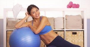 Donna giapponese sorridente che riposa sulla palla di allenamento fotografie stock libere da diritti