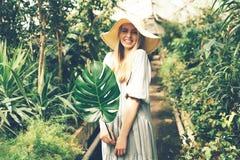 Donna in giardino di inverno tropicale con la foglia di monstera immagini stock libere da diritti