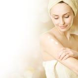 Donna giovane che applica crema d'idratazione Fotografie Stock