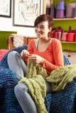 Donna giovane che si siede nel lavoro a maglia della presidenza Fotografia Stock Libera da Diritti