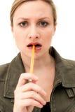 Donna giovane di pensiero o di progettazione con la penna immagine stock libera da diritti