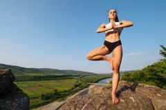 Donna giovane di yoga con l'ente muscolare perfetto che fa posa dell'albero Esercizio dell'equilibrio e di meditazione in natura  Fotografie Stock Libere da Diritti