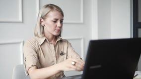 Donna giovane e felice che lavora al computer portatile ed alla risata Ragazza di modo divertendosi durante la compera online video d archivio