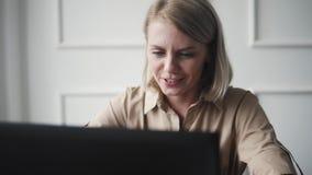 Donna giovane e felice che lavora al computer portatile ed alla risata Ragazza di modo divertendosi durante la compera online stock footage