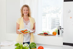 Donna gli che mostra alimento sano nella sua cucina Fotografie Stock Libere da Diritti