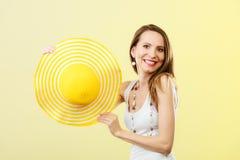 Donna in grande cappello giallo di estate Immagine Stock