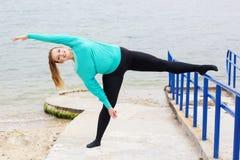 Donna grassa allegra che fa allungamento vicino al mare Fotografia Stock