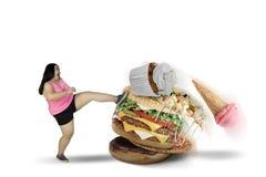 Donna grassa che dà dei calci agli alimenti saporiti sullo studio Immagine Stock Libera da Diritti