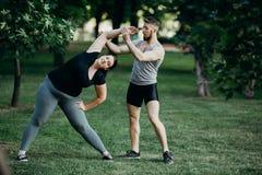 Donna grassa che fa yoga con l'istruttore di forma fisica Fotografia Stock