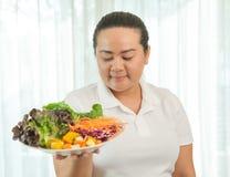 Donna grassa che mangia insalata Immagini Stock