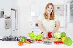 Donna grassa che produce insalata con la verdura Immagini Stock