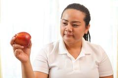 Donna grassa con la mela Immagini Stock