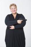 Donna grassa con una pistola in un vestito nero Fotografia Stock