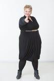 Donna grassa con una pistola in un vestito nero Immagini Stock
