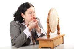 Donna grassa e di peso eccessivo che applica rossetto Immagine Stock