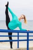 Donna grassottella allegra che fa allungamento vicino al mare Fotografia Stock
