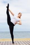 Donna grassottella allegra che fa asana di yoga vicino al mare Immagine Stock