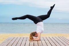 Donna grassottella allegra che fa verticale vicino al mare Immagini Stock