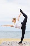Donna grassottella allegra che fa yoga vicino al mare Fotografia Stock