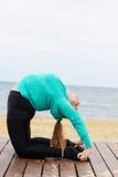 Donna grassottella che fa asana di yoga di hatha vicino al mare Immagini Stock