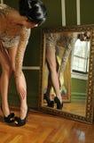 Donna graziosa in abito dell'annata che osserva nello specchio Fotografie Stock