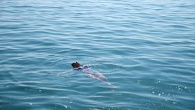 Donna graziosa bionda che gode dell'acqua nel mare aperto, galleggiante Vista da sopra Movimento lento archivi video