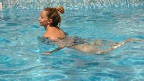 Donna graziosa bionda che gode dell'acqua nello stagno Vista da sopra Movimento lento video d archivio