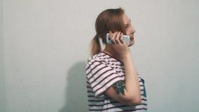 Donna graziosa in camicia a strisce con i tatuaggi che parla sullo smartphone sulla parete bianca stock footage