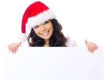 Donna graziosa in cappello di Santa che visualizza un segno Immagini Stock