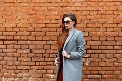 Donna graziosa in cappotto grigio ed occhiali da sole vicino ad un muro di mattoni fotografia stock