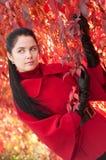 Donna graziosa in cappotto rosso alla sosta di autunno. Immagini Stock Libere da Diritti